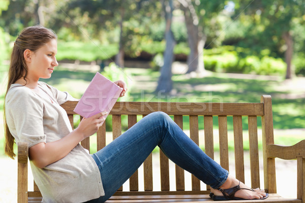Side view of a young woman reading a novel on a park bench Stock photo © wavebreak_media