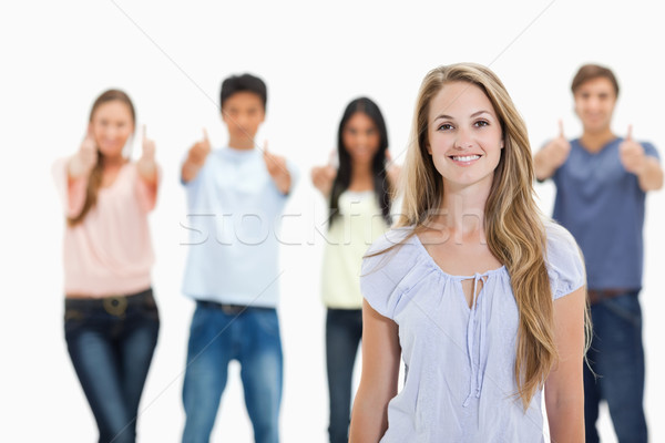 Close-up of woman smiling with people approving behind her against white background Stock photo © wavebreak_media