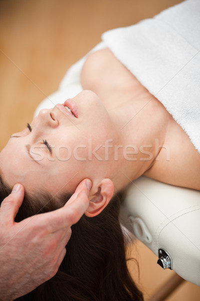 Woman lying on the back while being massaged on her head in a room Stock photo © wavebreak_media