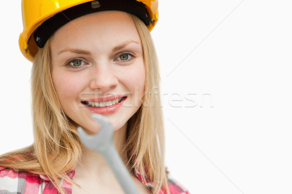 Close up of a woman holding a wrench against white background Stock photo © wavebreak_media
