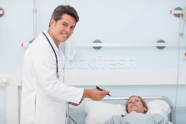 Doctor standing next to his patient in a hospital ward Stock photo © wavebreak_media