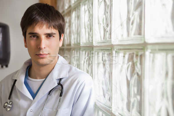 Smiling doctor leans against glass wall in hospital Stock photo © wavebreak_media