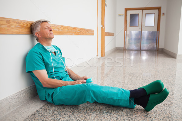 Doctor is sitting the floor of the corridor in the hospital while eyes closed Stock photo © wavebreak_media