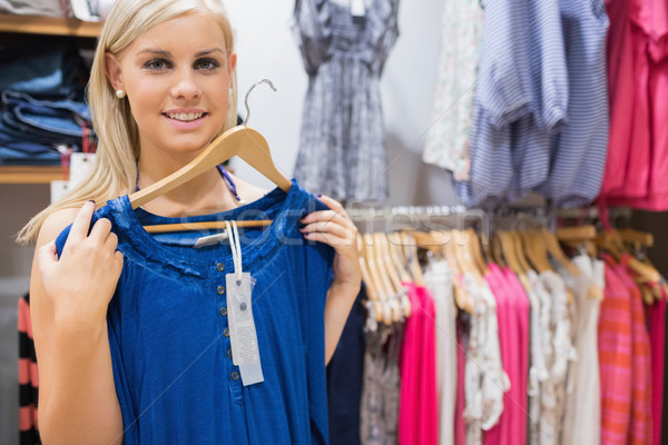 Stock photo: Woman holding up blue shirt and smiling in clothing store