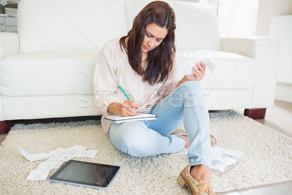 Young woman adding receipts on floor of living room Stock photo © wavebreak_media