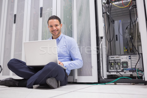 Smiling man sitting on floor checking servers with laptop in data center Stock photo © wavebreak_media