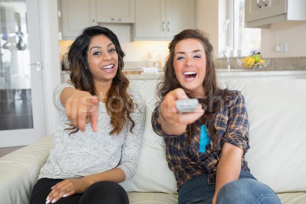 две женщины улыбаясь смеясь телевидение удаленных Сток-фото © wavebreak_media