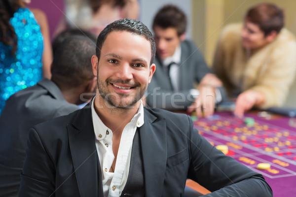 Gülen adam oturma rulet tablo Stok fotoğraf © wavebreak_media