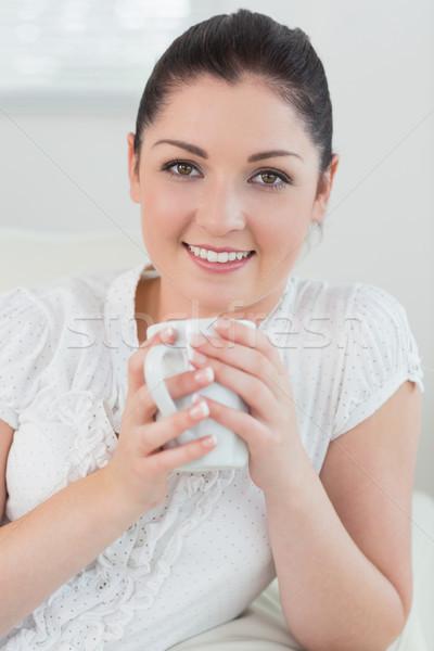 Heureux femme canapé salon mug Photo stock © wavebreak_media