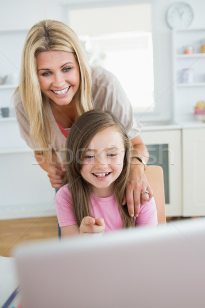 Little girl pointing at laptop and laughing with mother in the kitchen Stock photo © wavebreak_media