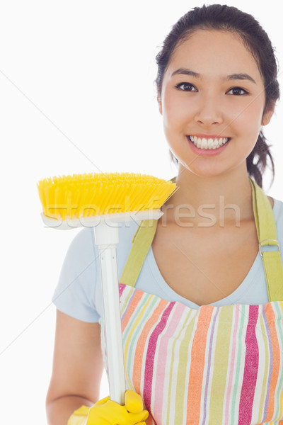 Smiling woman in apron with broom Stock photo © wavebreak_media