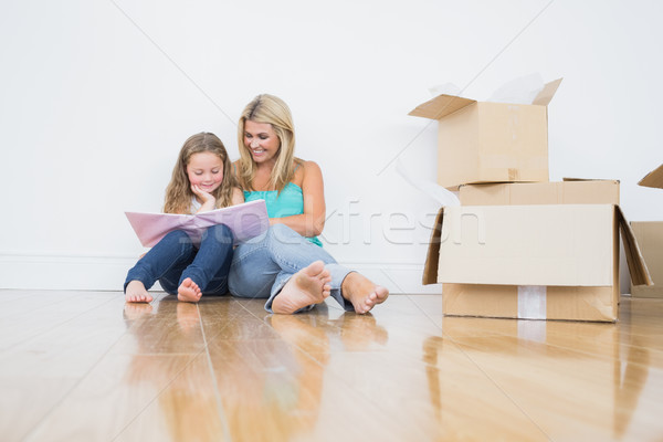 Mother and daughter reading a book together on the floor near moving boxes Stock photo © wavebreak_media