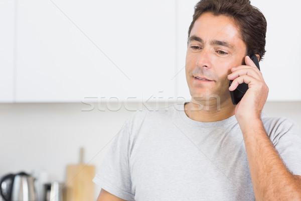 Man phoning in kitchen Stock photo © wavebreak_media