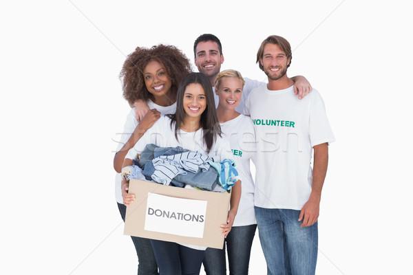 Smiling group of volunteers holding donation box Stock photo © wavebreak_media
