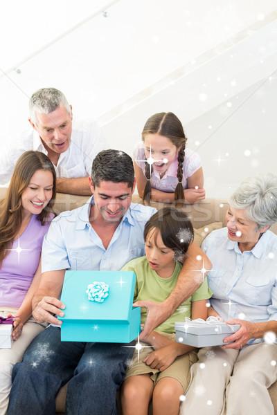Composite image of family gifting birthday present to man  Stock photo © wavebreak_media