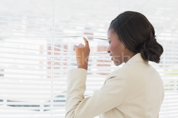 Businesswoman peeking through office blinds Stock photo © wavebreak_media