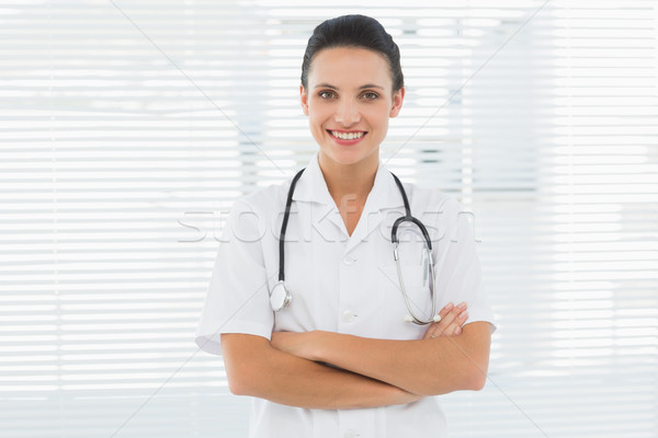 Smiling beautiful female doctor with arms crossed Stock photo © wavebreak_media