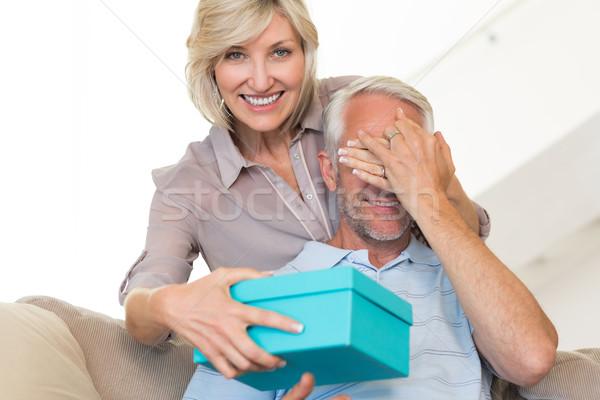 Glimlachende vrouw verrassend volwassen man geschenk sofa portret Stockfoto © wavebreak_media