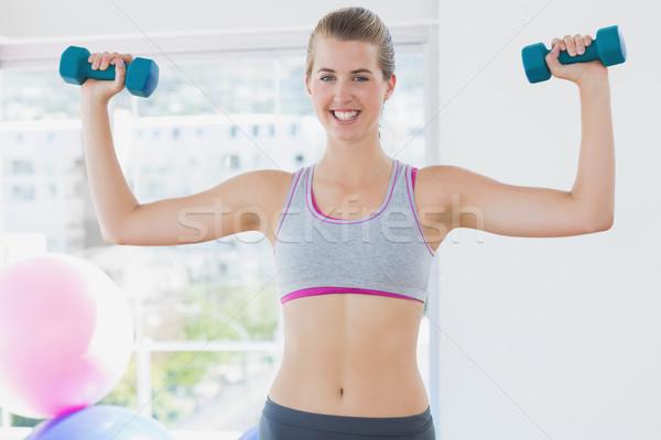 Smiling woman exercising with dumbbells in fitness studio Stock photo © wavebreak_media