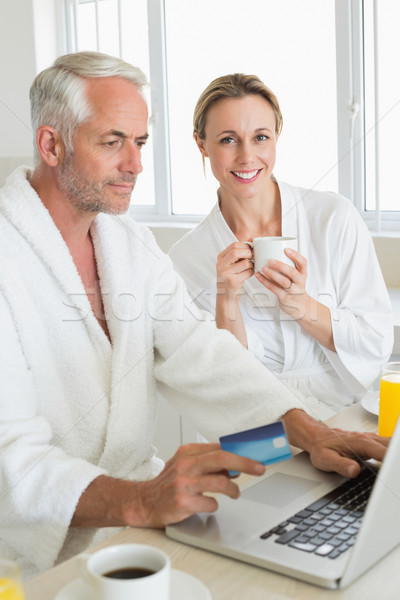 Stock photo: Smiling couple using laptop at breakfast in bathrobes