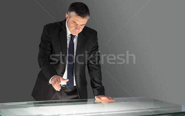 Concentrating businessman leaning on desk  Stock photo © wavebreak_media