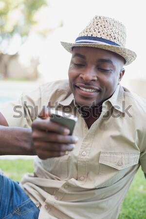 Smiling man relaxing in his garden texting on phone Stock photo © wavebreak_media