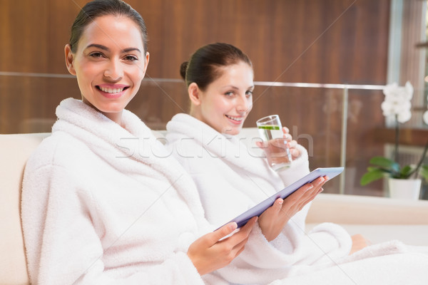 Women in bathrobes drinking water and text messaging Stock photo © wavebreak_media