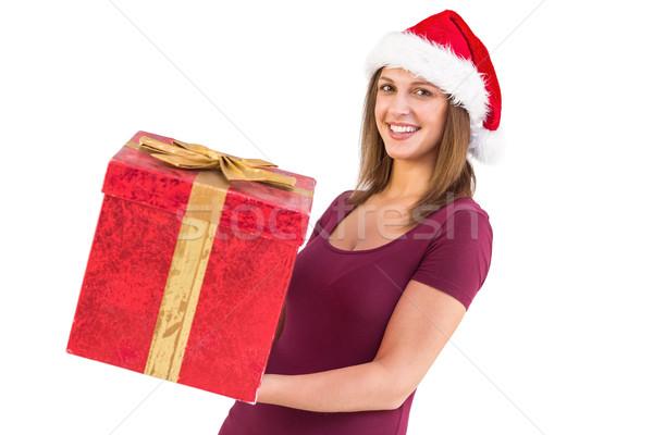 Pretty girl in santa hat holding gift box Stock photo © wavebreak_media