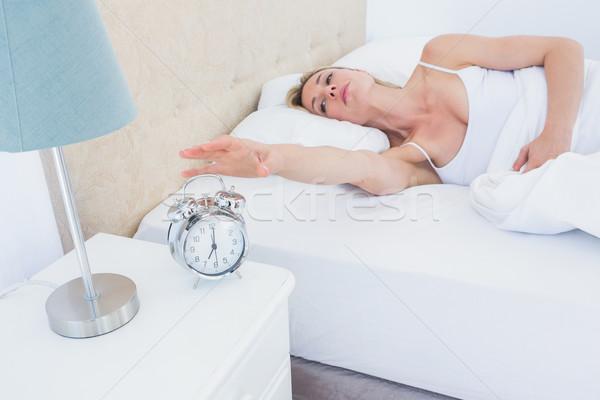 Sarışın kadın yatak çalar saat ev yatak odası kadın Stok fotoğraf © wavebreak_media