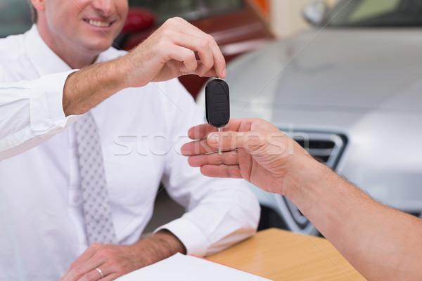 Smiling salesman giving a customer car keys Stock photo © wavebreak_media