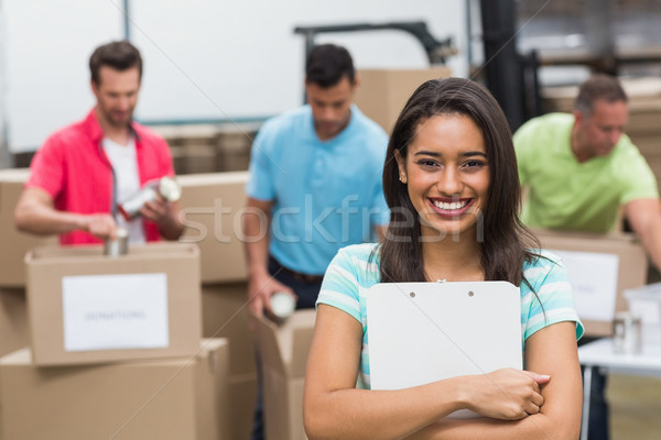 Stock photo: Smiling young female volunteer holding clipboard