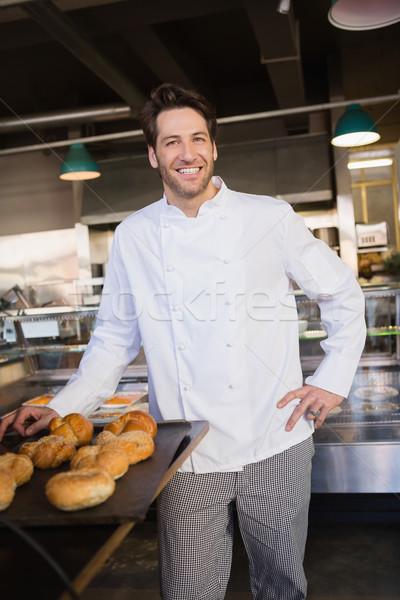 Happy baker standing near tray with bread Stock photo © wavebreak_media
