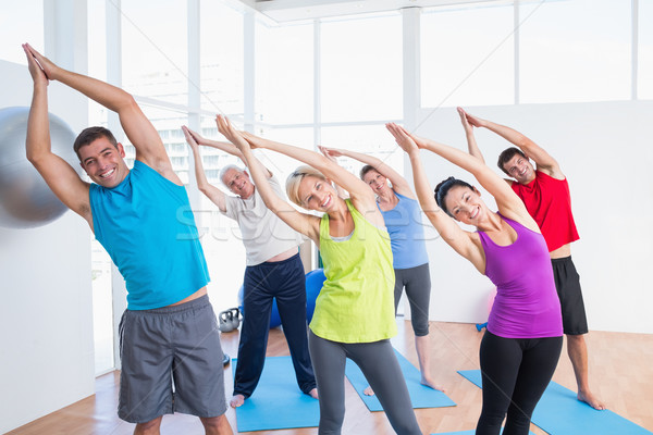 Happy people doing stretching exercise in yoga class Stock photo © wavebreak_media
