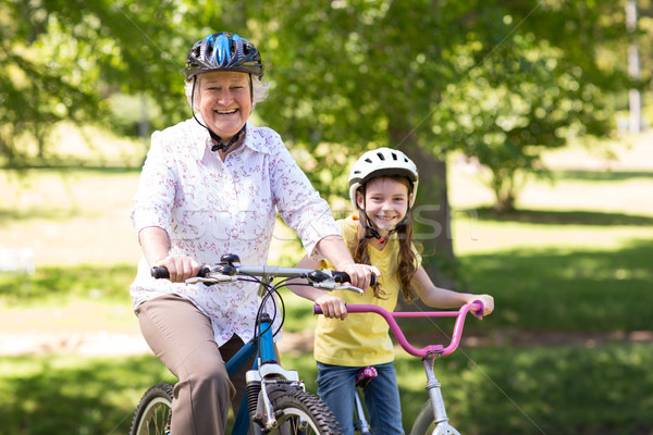 Happy grandmother with her granddaughter on their bike Stock photo © wavebreak_media
