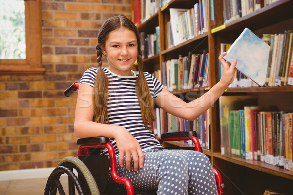 Stock photo: Girl in wheelchair selecting book in library