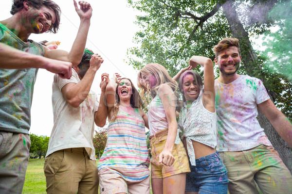 Happy friends throwing powder paint Stock photo © wavebreak_media