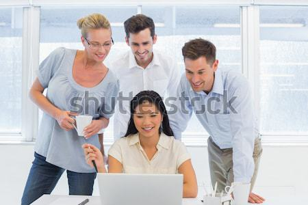 Co workers all looking at a laptop Stock photo © wavebreak_media