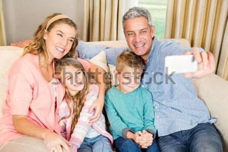 famille heureuse temps ensemble maison salon femme photo stock wavebreak media. Black Bedroom Furniture Sets. Home Design Ideas