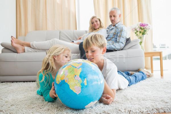 Siblings looking at globe on the floor Stock photo © wavebreak_media