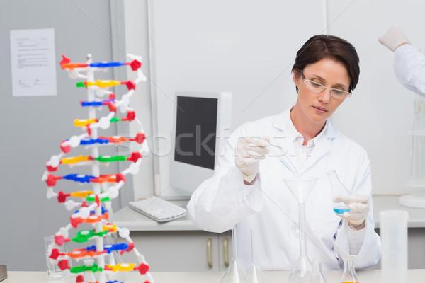 Scientist pouring chemical fluid in funnel Stock photo © wavebreak_media