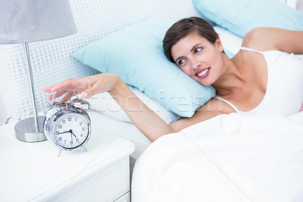 Happy woman extending hand to alarm clock  Stock photo © wavebreak_media