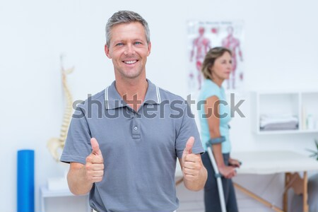 Doctor smiling at camera while his patient standing with crutch Stock photo © wavebreak_media