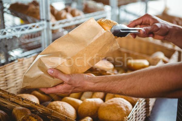 Smiling waiter taking bread with tongs Stock photo © wavebreak_media