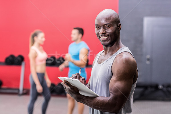 Uśmiechnięty muskularny trener piśmie schowek portret Zdjęcia stock © wavebreak_media