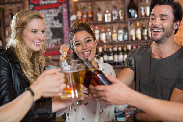 Cheerful friends toasting beer mugs and bottles Stock photo © wavebreak_media