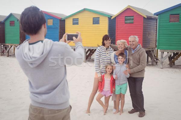 Férfi fényképezés család tengerpart áll telefon Stock fotó © wavebreak_media