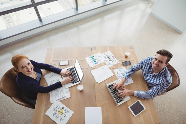 Overhead view of executives using laptop at desk Stock photo © wavebreak_media