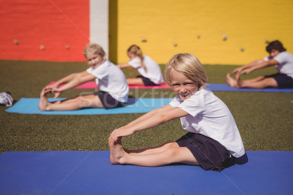 Portrait of happy schoolkid performing stretching exercise Stock photo © wavebreak_media