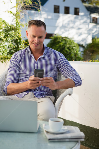 Happy man using mobile phone while sitting in cafe Stock photo © wavebreak_media