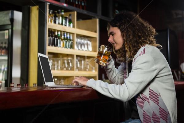Uomo birra utilizzando il computer portatile counter bar computer Foto d'archivio © wavebreak_media